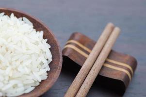 riz thaï avec des baguettes sur fond de bois