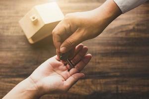 concept immobilier, banquier de l'agence à domicile donnant la clé de la maison au propriétaire