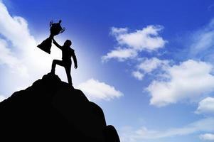 Personne silhouette montrant le trophée au sommet de la montagne photo