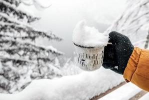 main dans un gant tricoté tenant une tasse de neige photo