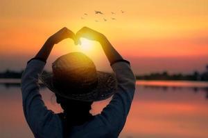 amour et concept heureux, silhouette de femmes en forme de coeur au coucher du soleil photo
