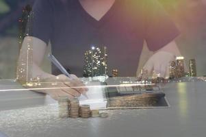 Double exposition de personne qui écrit sur table avec pile de pièces et ville de nuit