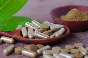 Médicament à base de plantes en pilule et capsule sur table en bois