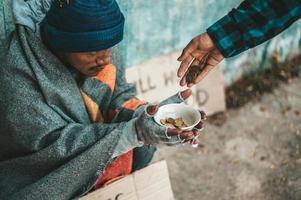 personne donne à un mendiant sur le bord de la route photo