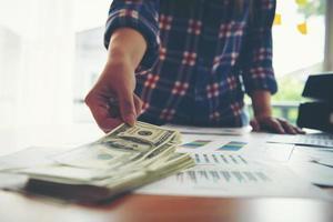 jeune femme d'affaires vérifie les billets en dollars