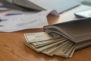 Billet de banque en dollars américains à l'intérieur du livre sur la table en bois photo