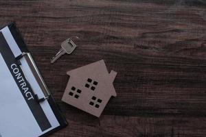 Immobilier et contrat papier avec clé de maison sur table en bois