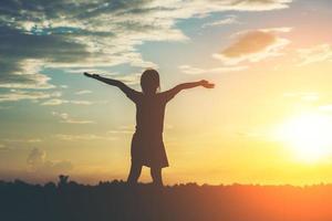 silhouette de petite fille levant les mains pour la liberté photo