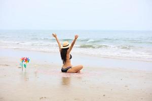 Femme levant les mains sur une plage exprimant le bonheur et la relaxation