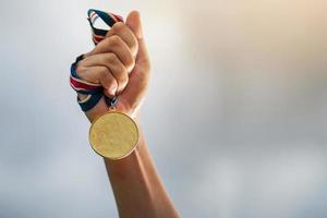 main tenant une médaille d'or photo