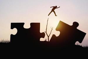silhouette de l'homme sautant à travers des pièces de puzzle photo