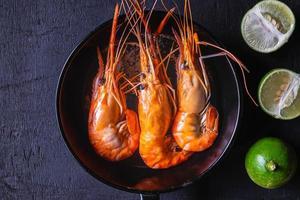 crevettes dans une casserole sur fond sombre photo
