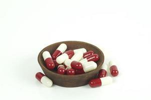Capsules rouges et blanches dans une coupe en bois isolé sur fond blanc photo