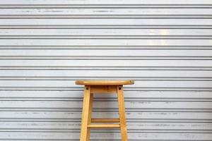 Chaises hautes rondes vintage en bois devant la porte métallique
