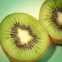 Tranches de kiwi isolé sur fond vert, technique de couleur pop art photo