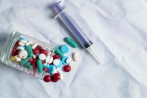 pilules dans une tasse et une seringue