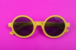verres jaunes isolés sur fond rose photo