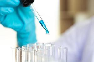 scientifique, remplissage de tubes à essai avec compte-gouttes