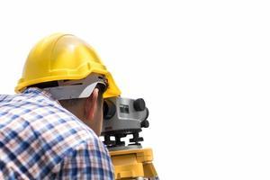 Ingénieur à la recherche d'instrument de mesure de niveau isolé sur fond blanc photo