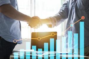 hommes d & # 39; affaires se serrant la main et graphique des finances photo