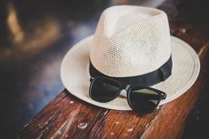 chapeau et lunettes de soleil sur banc en bois à la gare