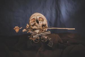nature morte avec un pistolet croisé et un crâne photo