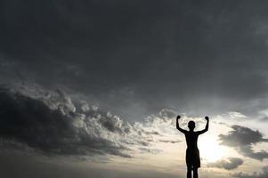 silhouette d'un garçon levant les mains dans le ciel photo