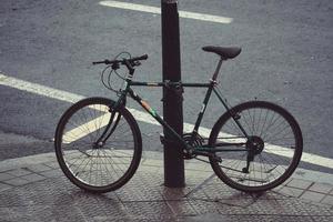 vélo enchaîné à un poteau photo