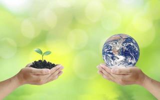 échange de planètes entre les mains des humains avec de jeunes plantes entre les mains des humains, le concept du jour de la terre et la conservation de l'environnement. éléments de cette image décorés par la nasa. photo