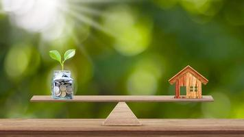 Planter des arbres dans des bouteilles claires pour économiser de l'argent sur une table en bois et des idées de croissance d'entreprise floue fond vert photo