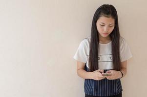 jeune fille asiatique à l'aide d'un téléphone intelligent photo
