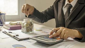 Les hommes d'affaires mettent des pièces dans une tirelire pour financer leur entreprise avec des idées durables d'économie d'argent et d'investissement photo