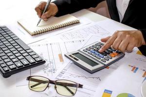 Gros plan de femmes utilisant des calculatrices pour créer des rapports comptables par la fenêtre dans leur propre maison, des concepts de calcul des coûts et des concepts de travail à domicile photo