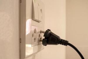 les dangers de l'utilisation de l'électricité dans votre maison ou votre bureau, y compris les mains noires qui ne sont pas complètement branchées sur le mur blanc photo