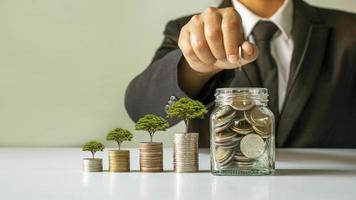 planter un arbre sur un tas d'argent et homme d'affaires, homme économisant de l'argent, idées d'économie d'argent pour un investissement futur