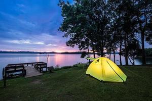 tente près de l'eau au coucher du soleil photo