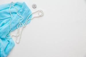 vue de dessus du tissu bleu et perles et rouge à lèvres
