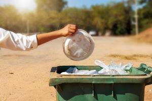 Gros plan d'un bénévole ramassant joyeusement des déchets en plastique dans un parc avec une idée de bénévolat pour nettoyer photo