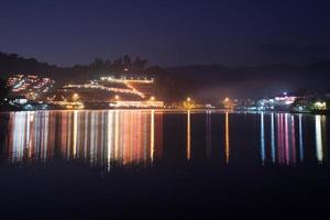 Réflexion des lumières du village coloré sur l'eau