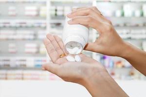 main du médecin avec une bouteille de pilules blanches