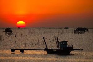 silhouette de bateau de pêche et un coucher de soleil
