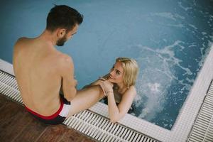 jeune couple de détente au bord de la piscine intérieure