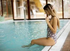 belle jeune femme assise au bord de la piscine photo