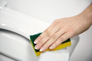 Jeune femme nettoyant un siège de toilette avec une éponge photo
