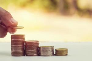 Main mettant de l'argent sur une pile de pièces photo