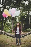 jeune femme hipster assis sur une branche d'arbre avec des ballons colorés photo