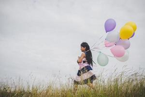petite fille jouant avec des ballons sur le champ de prés photo