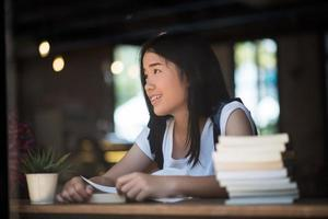 Young woman reading book assis à l'intérieur dans un café urbain photo