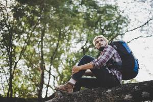 jeune homme hipster assis sur une branche d'arbre dans le parc photo
