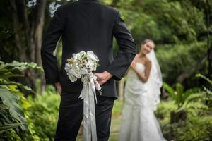 Portrait d'un marié cachant un bouquet de fleurs derrière son dos pour surprendre la mariée
